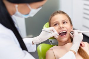 young girl gets a dental exam