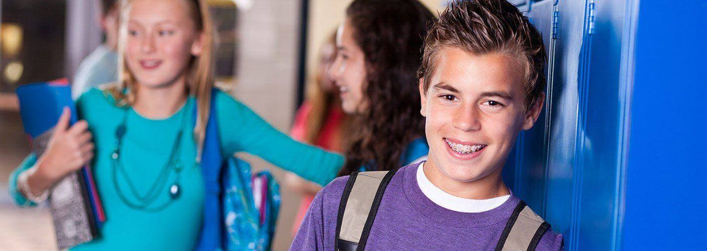 Teen boy with braces at school