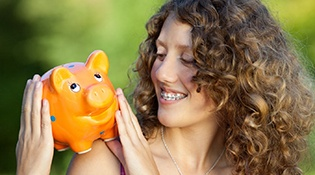 Woman with braces smiling at piggy bank on shoulder