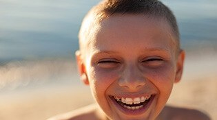 Young boy with braces at beach