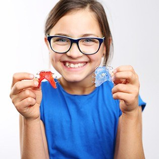 Little girl holding two retainers