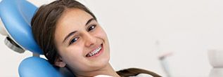 Smiling girl in orthodontic chair