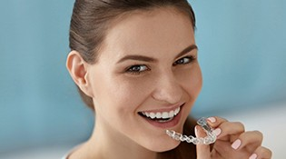 A young woman smiling as she prepares to insert a clear aligner into the top arch of her smile