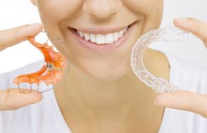 A woman holding two types of orthodontic retainers.