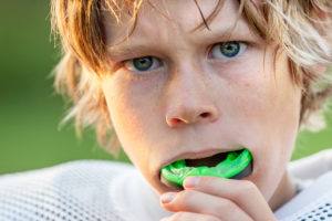 Young male who is taking out mouthguard after physical activity