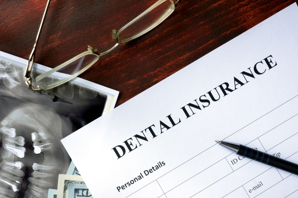 Dental insurance paperwork lying next to glasses and X-ray